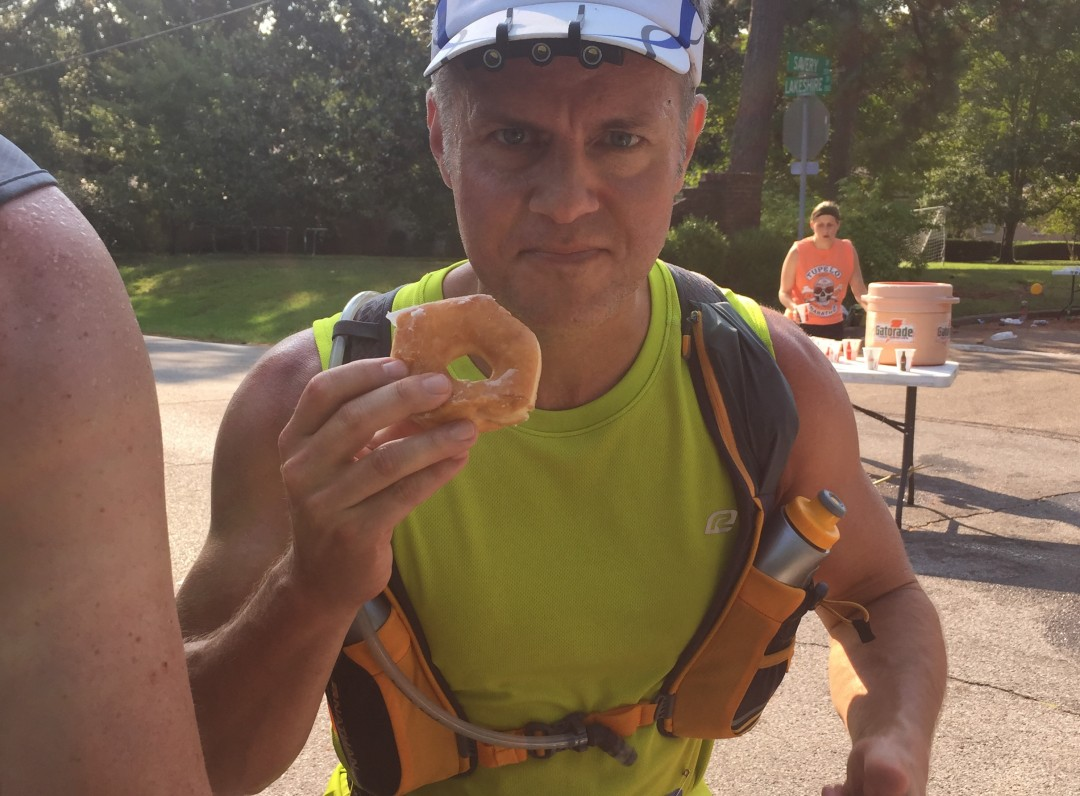 Joe enjoys a donut at an aid station during the 2015 Tupelo Marathon